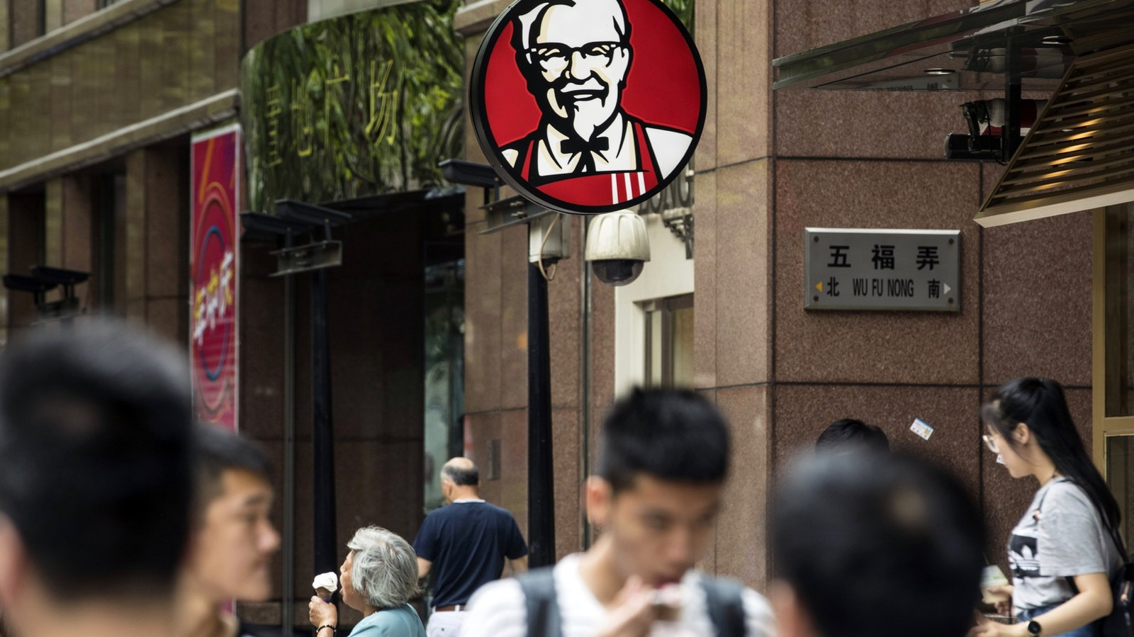 Pedestrians walk past a Yum Brands KFC restaurant in Shanghai. Photo: Bloomberg
