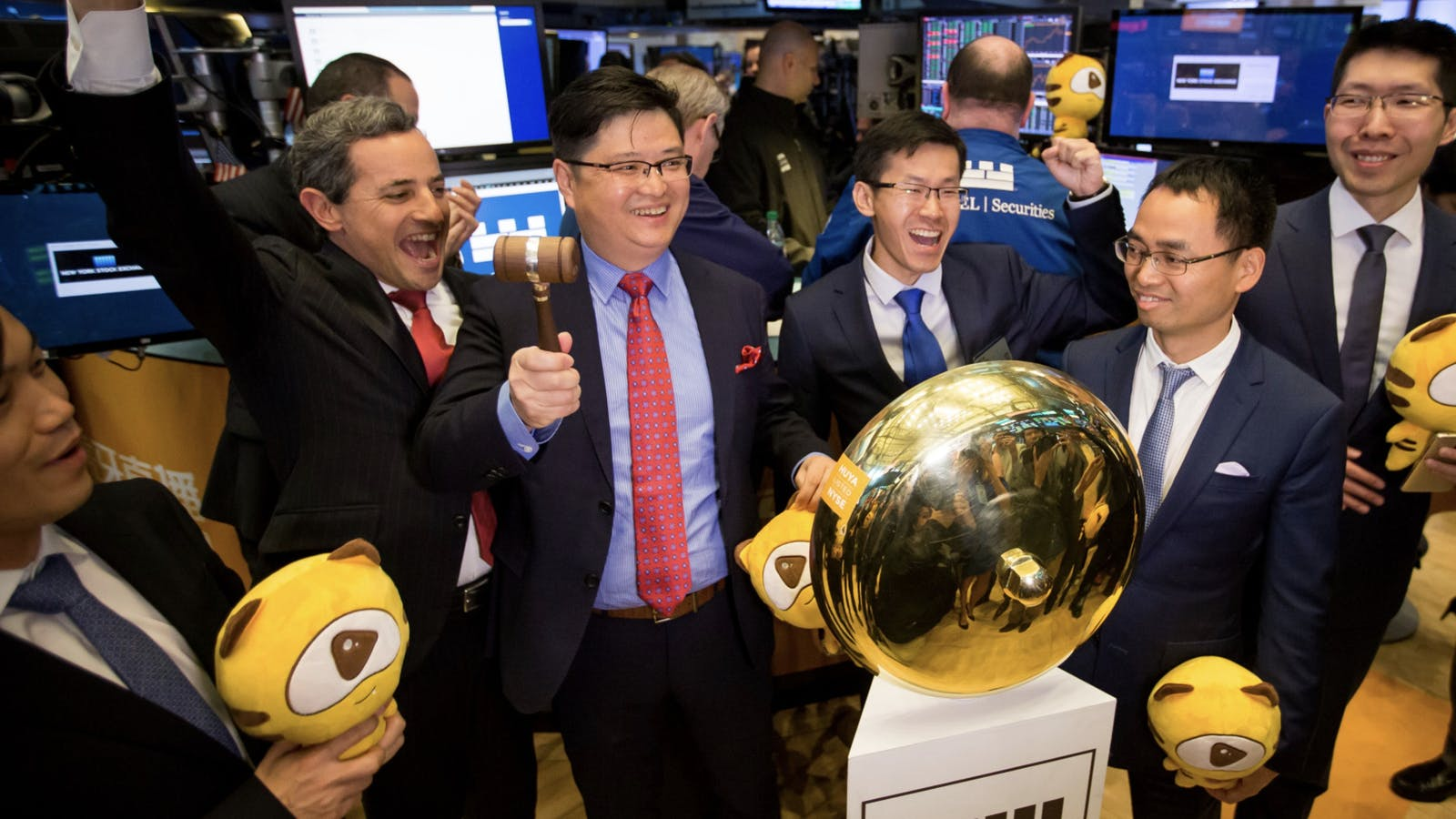 YY CEO Li Xueling, holding the hammer,  at the New York Stock Exchange last year when YY's subsidiary Huya went public. Photo by Bloomberg