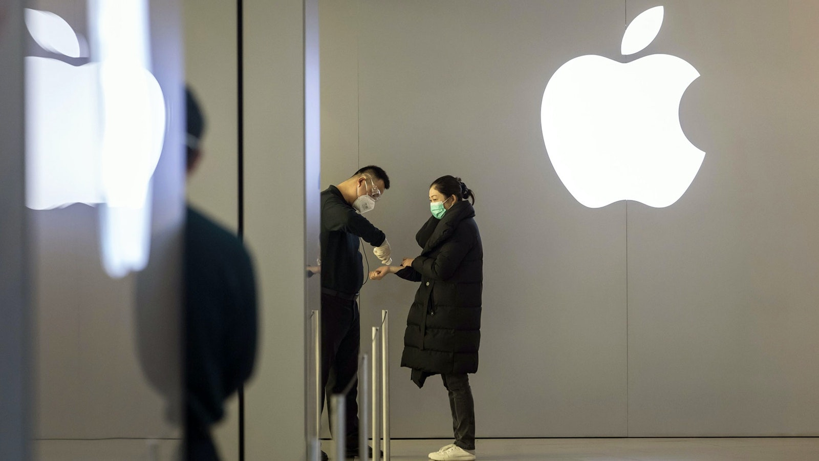 An employee wearing a protective mask takes the temperature of a customer at an entrance to an Apple store in Shanghai, China. Photo by Bloomberg.
