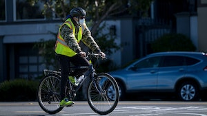 A cyclist wearing a protective mask rides through San Francisco on March 25, 2020.