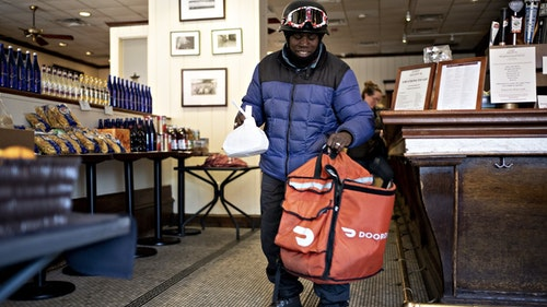 A DoorDash delivery person picking up an order in Washington D.C. Photo by Bloomberg.