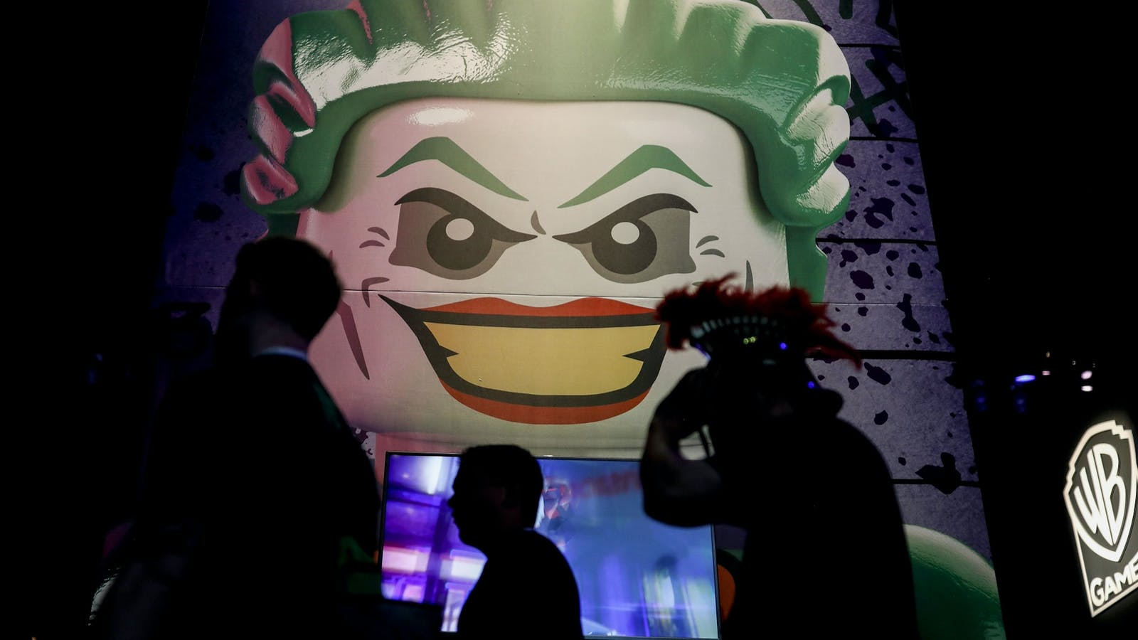 Attendees at the 2018 E3 conference in Los Angeles walk past a booth for Warner Bros. Interactive Entertainment. Photo by Bloomberg