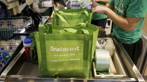 Instacart workers filling an order at a supermarket in Los Angeles. Photo by Bloomberg