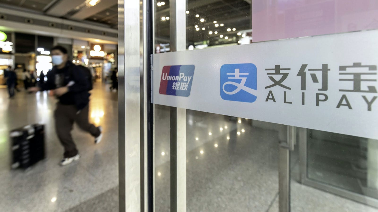 Signs for the Alipay service at a train station in China. Photo by Bloomberg
