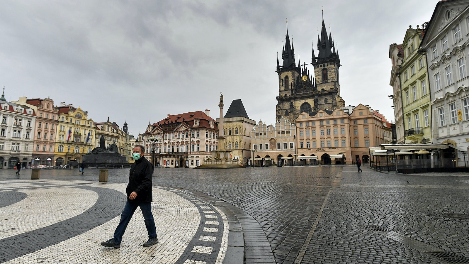 In typically tourist-filled Prague, Czech Republic, a man crosses a nearly empty Old Town Square. Photo: AP