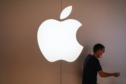 A pedestrian walks past an Apple retail store in Shenzhen. In recent months, Apple has resumed sending some U.S. employees to China to meet with its manufacturing partners. Photo: Associated Press
