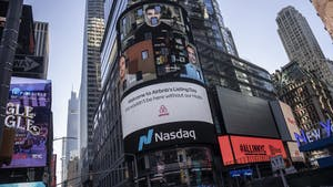 Airbnb's founders displayed on Nasdaq's Times Square screen in New York today. Photo by Bloomberg