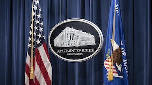 The Justice Department's sign at a press conference. Photo by Bloomberg