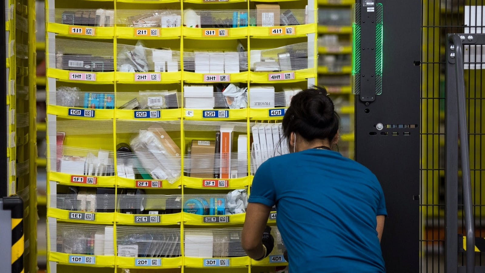 A worker at a picking station at an Amazon warehouse. Photo by Bloomberg