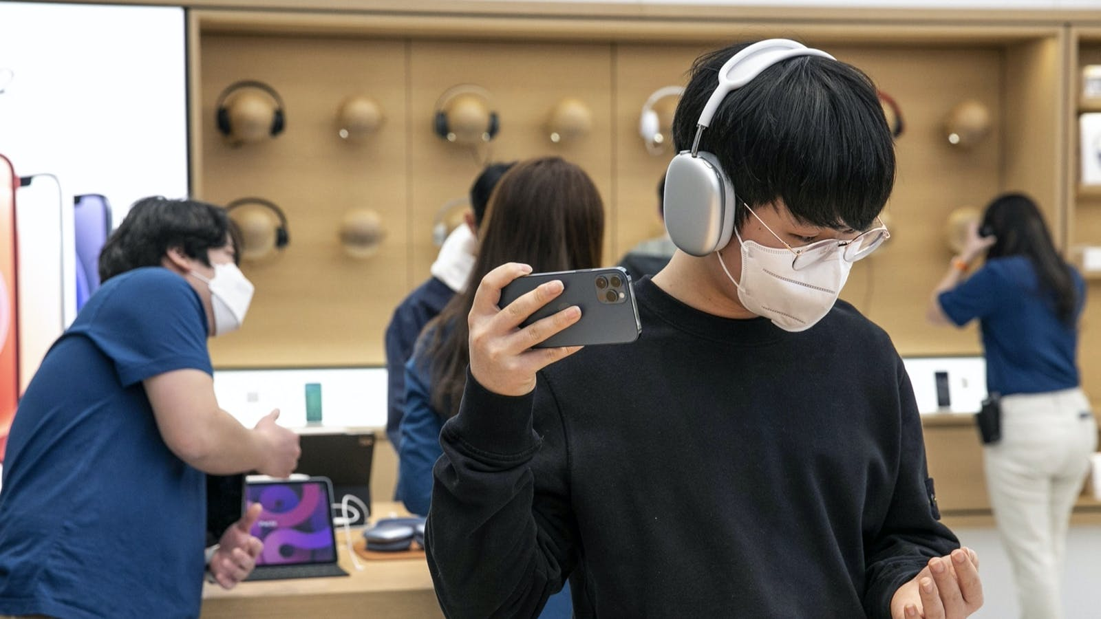A customer wearing a pair of AirPods Max headphones at an Apple store in South Korea. Photo by Bloomberg