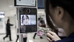 An employee uses a facial recognition device as she swipes her badge to enter the assembly line area at a Pegatron factory in Shanghai in 2016. Photo by Bloomberg.
