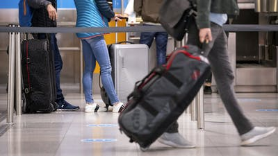 Travelers with their suitcases at a check-in counter at Munich airport. Photo by AP.