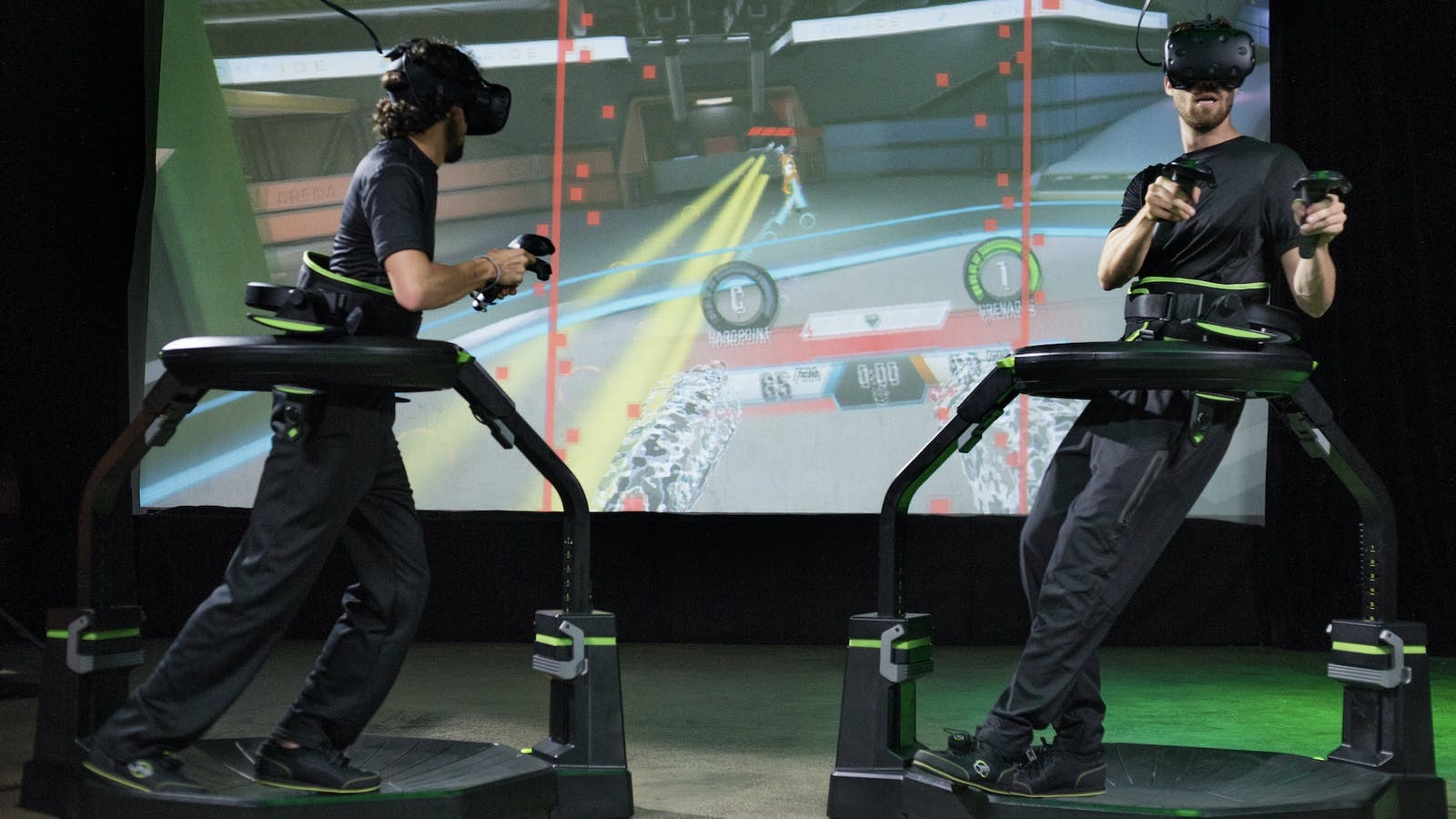 Two VR players using Virtuix Omni Pro treadmills and HTC Vive headsets. Photo by Virtuix