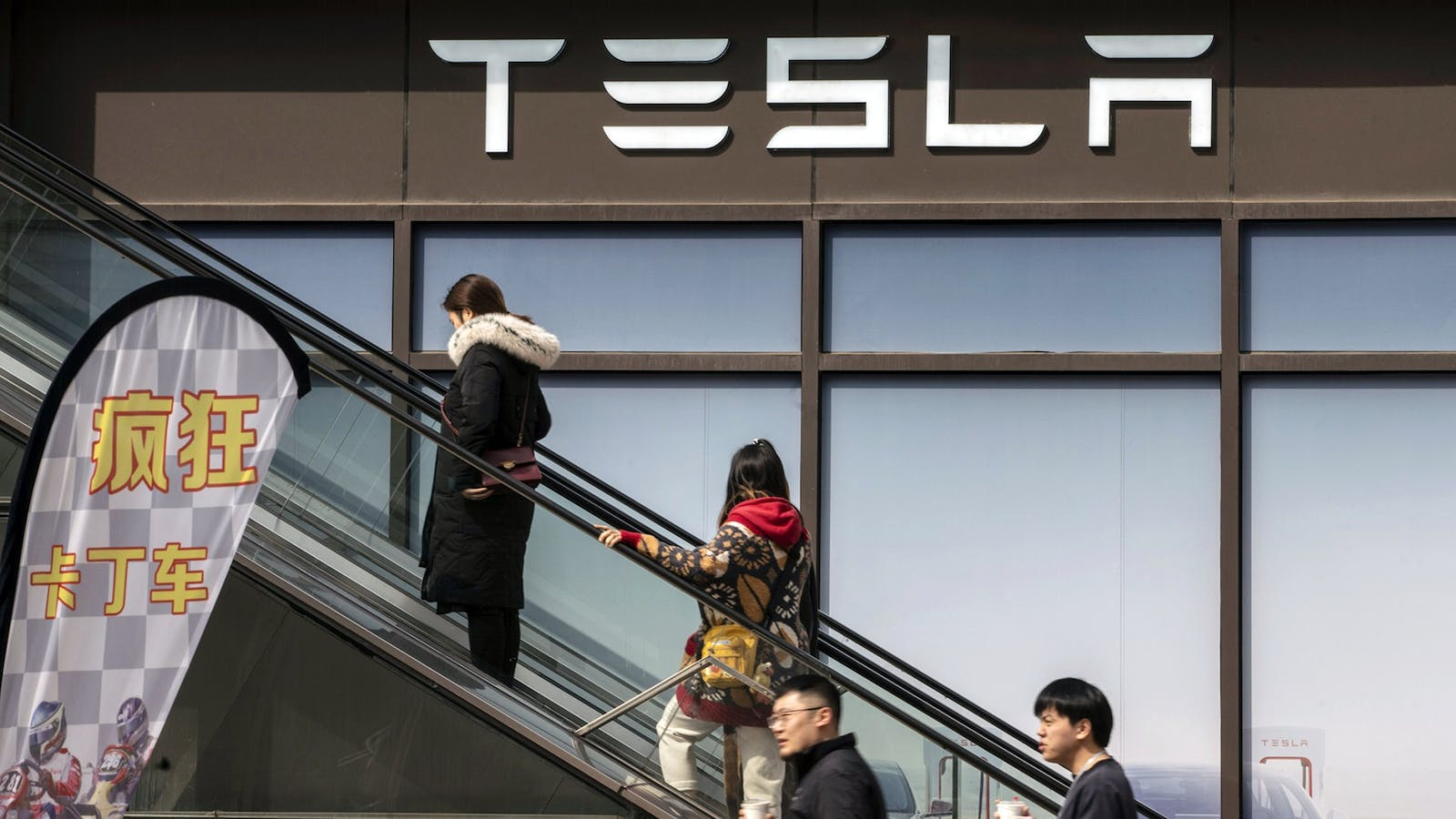 Shoppers in front of the Tesla showroom at a shopping plaza in Shanghai, China, in March. Photo by Bloomberg.