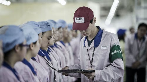 A supervisor holds checks an employee's badge during roll call at a Pegatron factory in Shanghai. Photo by Bloomberg
