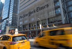 Taxis pass in front of the New York Times Co. headquarters in New York. Photo: Bloomberg