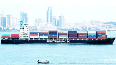 A container ship sailing past the city of Qingdao in east China's Shandong province last month. Photo by AP.