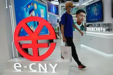 A visitor passes by a logo for the e-CNY, a digital version of the Chinese Yuan, displayed during a trade fair in Beijing on Sunday, Sept. 5. Photo: AP